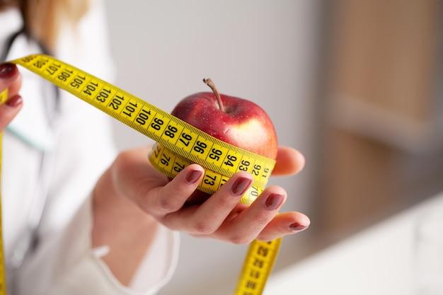 白人女性の手でリンゴを測定する際のクローズアップ。
