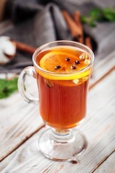 Крупным планом на марокканский чай с лимоном и специями в стеклянной кружке