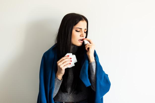 Крупным планом на упаковке таблеток в руке больной молодой женщины, лежа на диване
