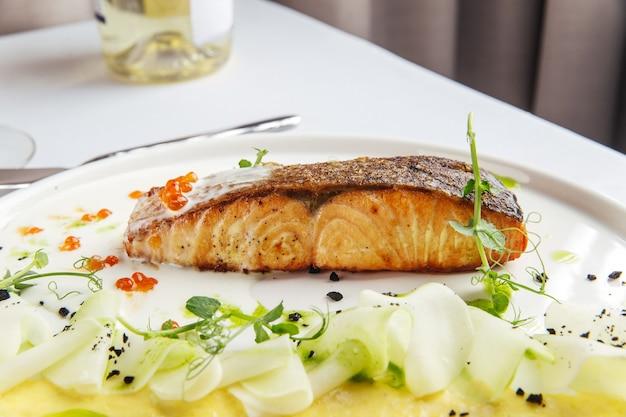 マッシュポテトと白い皿にキャビアとローストサーモンへのクローズアップ