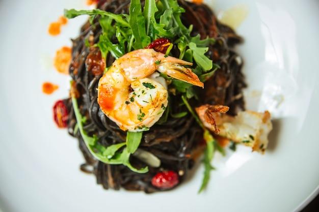 Крупным планом на спагетти с креветками и рукколой на белой тарелке