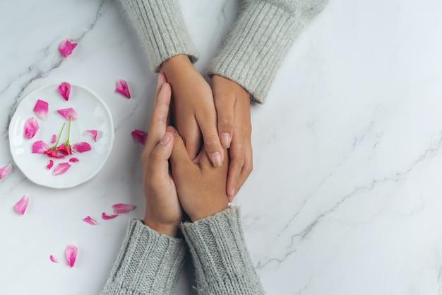テーブルで手をつないでいる2人の若い恋人のクローズアップ。