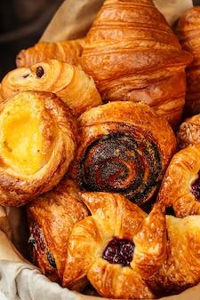 Крупным планом на разнообразие сладких свежих запеченных булочек в корзине