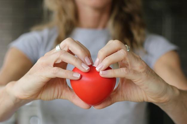 Крупным планом на руках женщины держит красное сердце