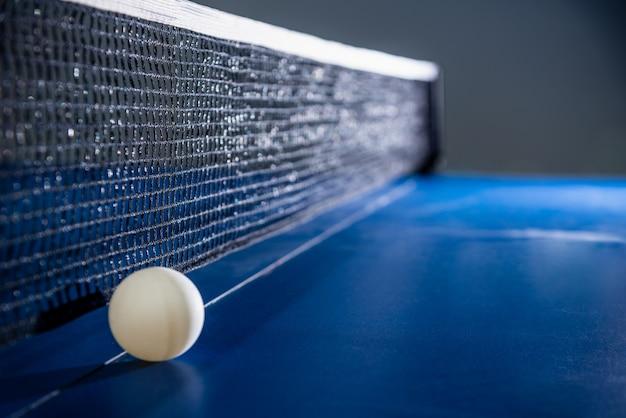 검은색 그물이 있는 파란색 탁구대에 흰색 공 하나를 닫고 탁구 패들은 스포츠 경기 장비 실내 활동 및 개념 배경을 위한 운동입니다.