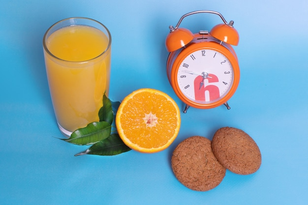 Closeup of an orange alarm clock with a glass of orange juice, fresh ripe fruit cut in half, oatmeal cookies on a blue background. organic and healthy breakfast concept.