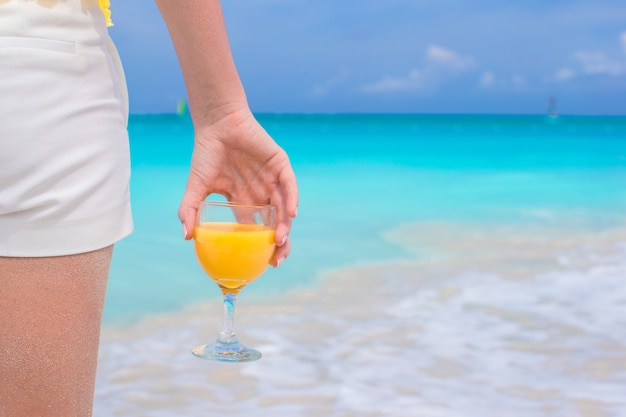 Closeup orange juice in a female hand on background of the sea