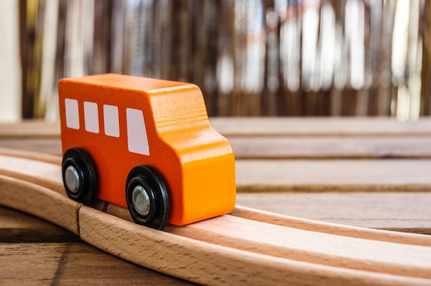Closeup of an orange wooden toy car on the tracks under the lights