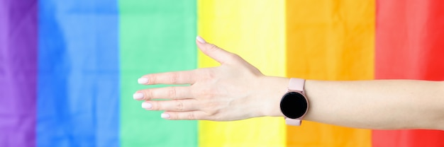 Closeup of outstretched hand with wristwatch against lgbt flag background. lgbt rights concept