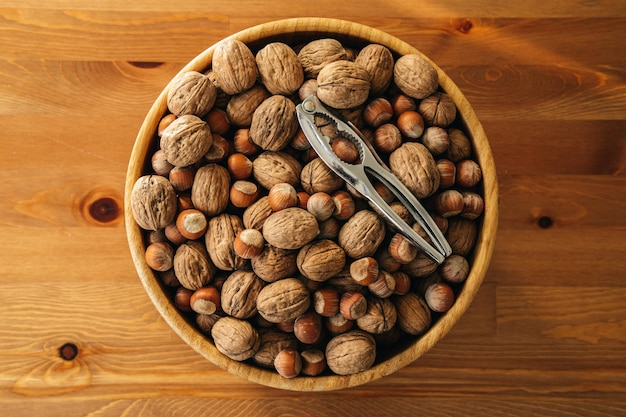 Closeup overhead shot of nuts with a nutcracker in a wooden plate on a wooden table