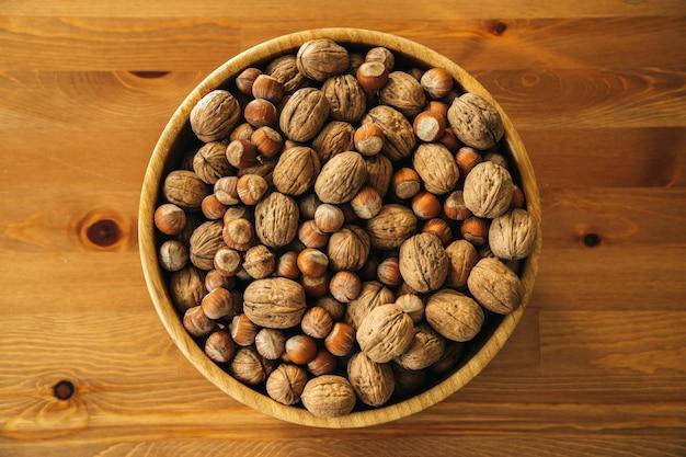 木製のテーブルの上の木の板のナッツのクローズアップオーバーヘッドショット