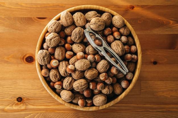 木製のテーブルの上の木の板にくるみ割り人形とナッツのクローズアップオーバーヘッドショット