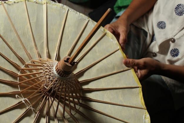 Colpo sopraelevato del primo piano di una persona che fa un ombrello di carta tailandese tradizionale