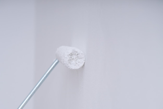 Closeup paint roller with white paint on clean wall with copy space