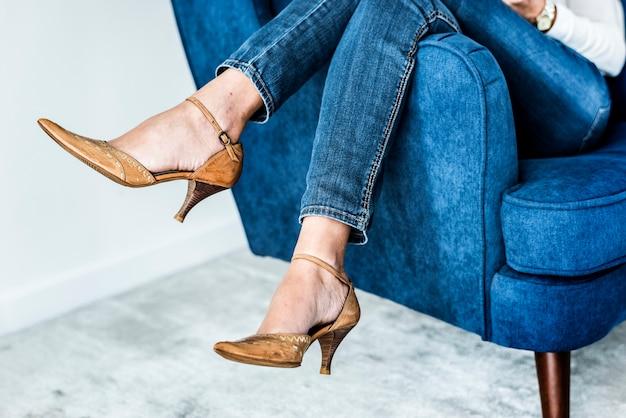 Closeup pair of legs on the sofa wearing heels