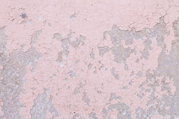 Closeup pale color and peeling of painted pink cement wall texture background