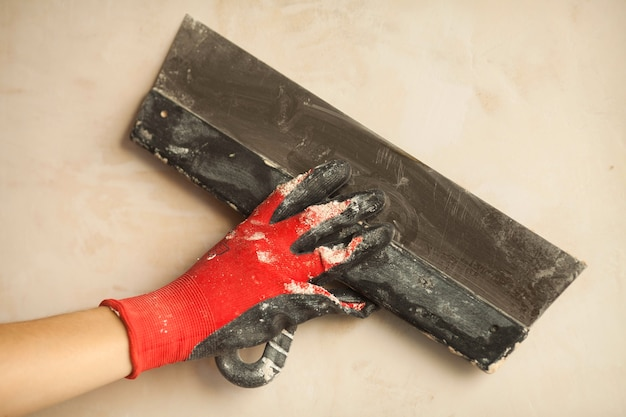Closeup of palette-knife or scraper and cement filling for house renovation construction in hands of handyman and worker fixing interior wall, with blurred background and copy space