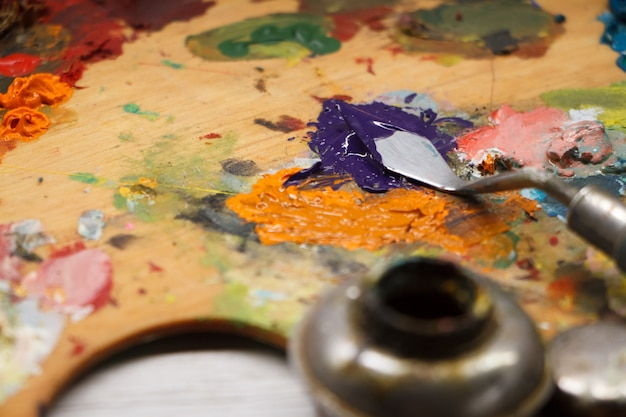 Closeup of palette with colorful paints and spatula on white surface