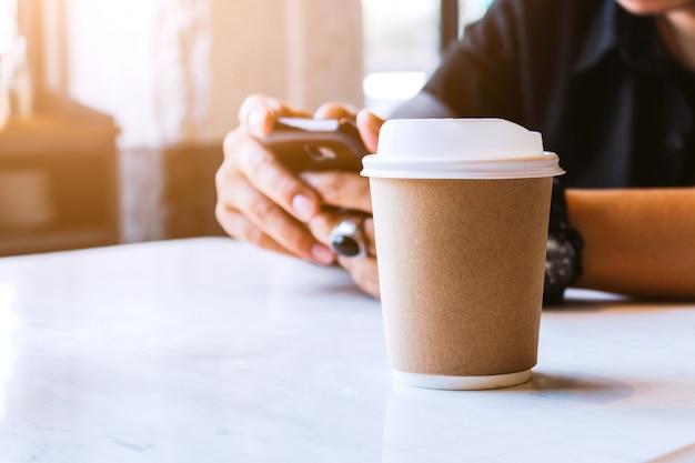 カフェでホットコーヒーのクローズアップの紙コップ