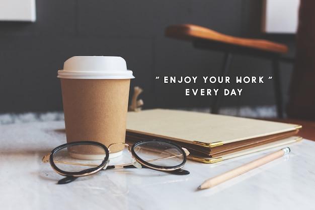ホットコーヒー、ノート、カフェの白いテーブルの上のグラスのクローズアップ紙コップ