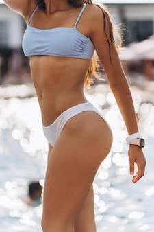 Parti del primo piano del modello sexy del corpo femminile in un bikini bianco