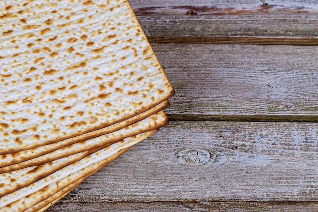 Closeup of passover matzah background matzoh over wooden table.