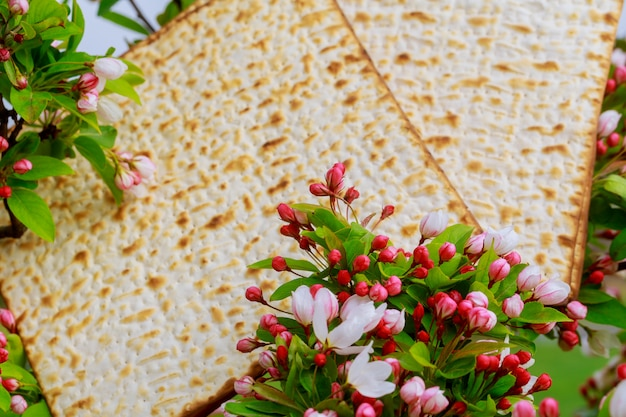 Closeup of passover matzah background matzoh over wooden table.