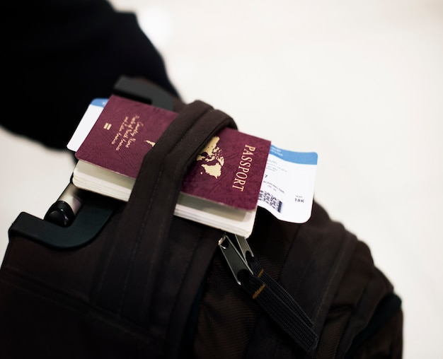 Closeup of passport with plane ticket on luggage