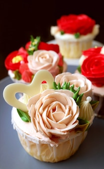 Closeup pastel pink rose shaped frosting cupcake with another in the backdrop