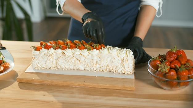 Closeup the pastry chef puts fresh strawberries on a meringue cake with cream