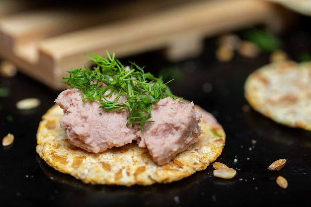 Closeup of pate on a cracker with herbs on the table under the lights with a blurry