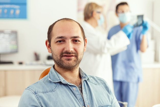 Closeup of patient man looking into camera waiting for doctors to start stomatology surgery sitting on dental chair