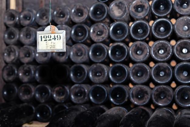セラーの行でほこりの多いワインのボトルの底からのクローズアップパターン