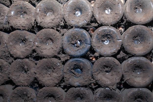 ワイン倉庫のセラーで行の古い暗いほこりの多いワインのボトルの底からのクローズアップパターン。古い珍しいワイン、排他的なコレクションの珍しいボトルと概念の金庫室