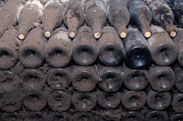 ワイナリーのセラーで行の古い暗いほこりの多いワインのボトルの底からのクローズアップパターン。古い珍しいワイン、排他的なコレクションの珍しいボトルと概念の金庫室