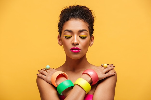 Closeup peaceful mulatto woman with closed eyes and pink lipstick posing on camera with crossed hands on shoulders, over yellow wall