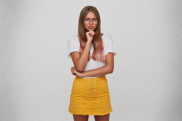Il primo piano della giovane donna attraente pensierosa indossa la maglietta, la gonna gialla e gli occhiali tiene le mani piegate e pensa isolato sopra il muro bianco
