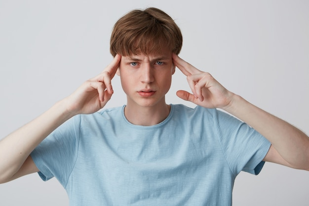 Closeup of pensive tensed young man wears blue t shirt touching his temples, thinking and having a headache isolated over white wall