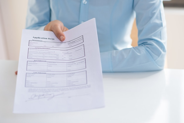 Closeup of person giving signed application form to viewer