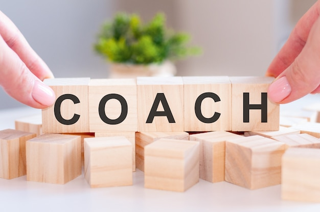 Closeup of person hand holding the word coach on wooden table.