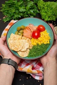 Closeup of a person holding a bowl of salad with salmon, crackers and vegetables under the lights