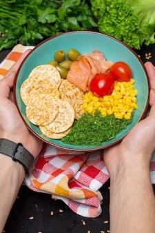 Primo piano di una persona che tiene una ciotola di insalata con salmone, cracker e verdure sotto le luci