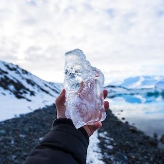 Primo piano di una persona che tiene il ghiaccio in islanda con uno sfondo sfocato