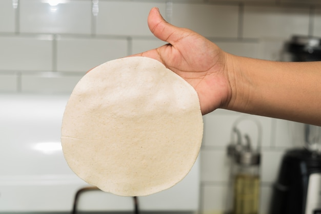 Closeup of a person holding a thin round dough in a kitchen under the lights