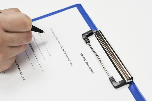 Primo piano di una persona che firma un accordo di concerto