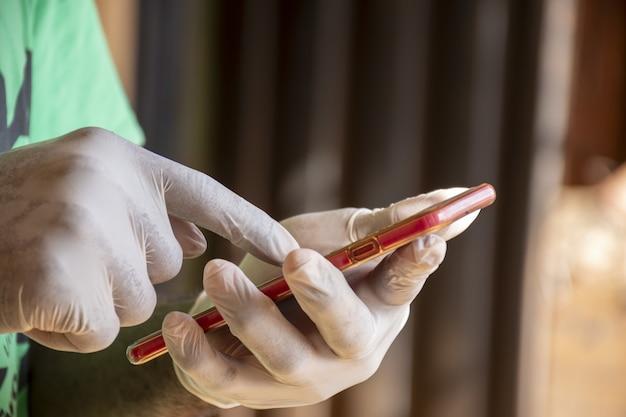 Primo piano di una persona che utilizza uno smartphone con guanti in lattice accesi sotto le luci - covid-19