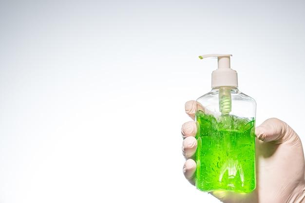 Primo piano di una persona con un guanto di lattice che tiene un disinfettante per le mani verde sotto le luci