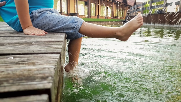 Closeup photo of 3 years old little boy sitting on the wooden pier and holding his feet in river water. child splashing in lake with legs