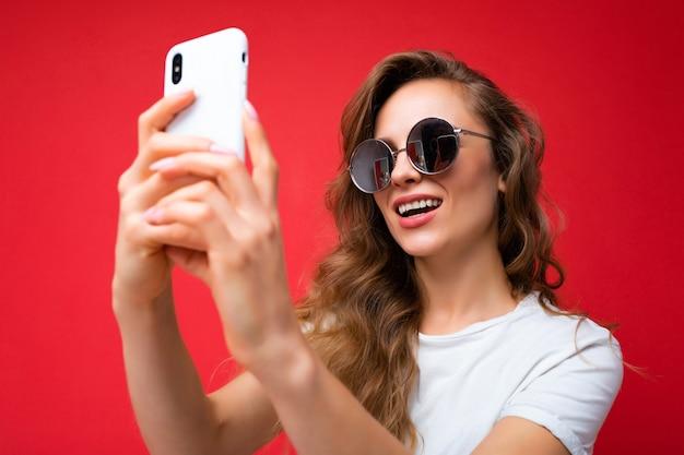Closeup photo of amazing beautiful young blonde woman holding mobile phone taking selfie photo using