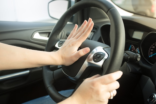Closeup photo of annoyed woman driving car and honking